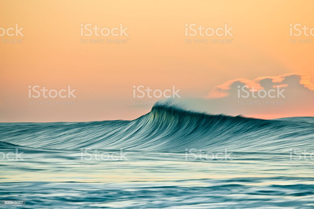Wind swept breaking wave in the golden light of sunrise. stock photo