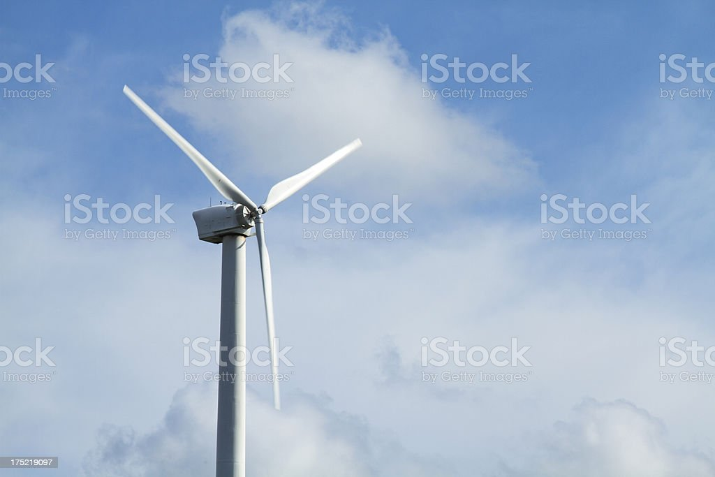 Wind turbine against blue sky royalty-free stock photo