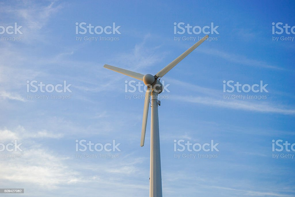 wind turbine against partly cloudy blue sky stock photo