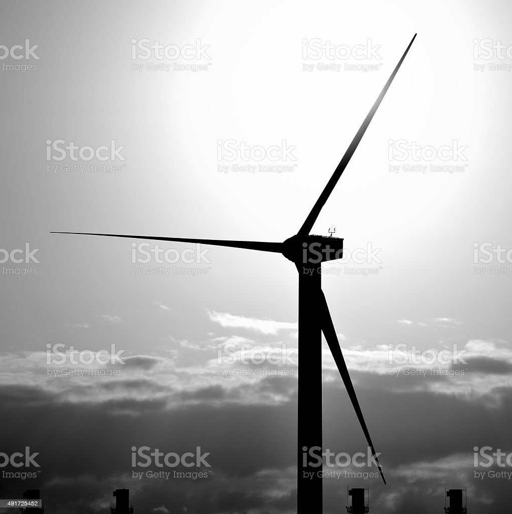 Wind turbine and chimneys on great sun at dawn stock photo