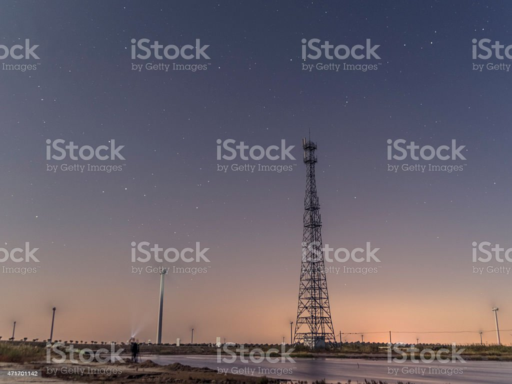 wind turbine and electrical towers at night stock photo