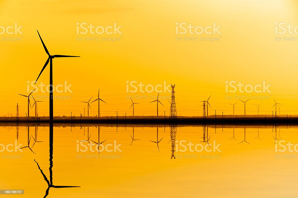 wind turbine and electrical towers on sunset royalty-free stock photo