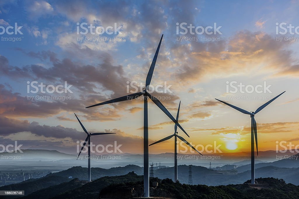 wind turbine and electrical towers on sunset stock photo