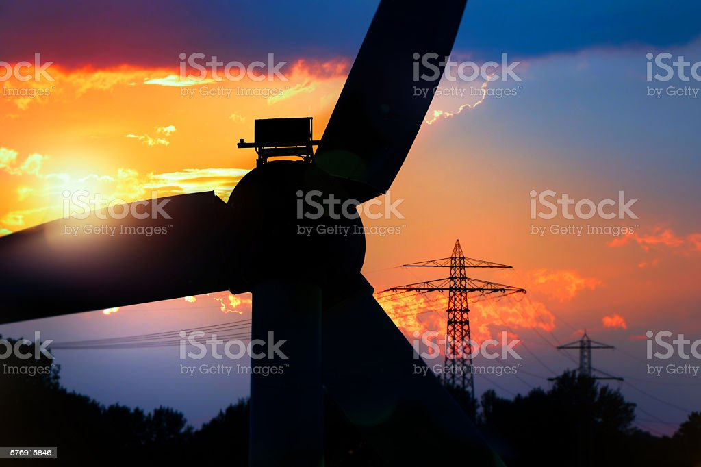 Wind Turbine and pylons silouette stock photo
