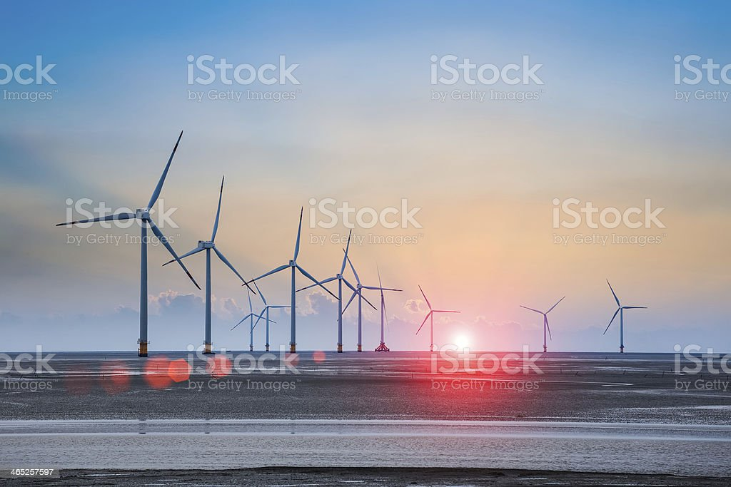 wind turbine farm with rays of light at sunset stock photo