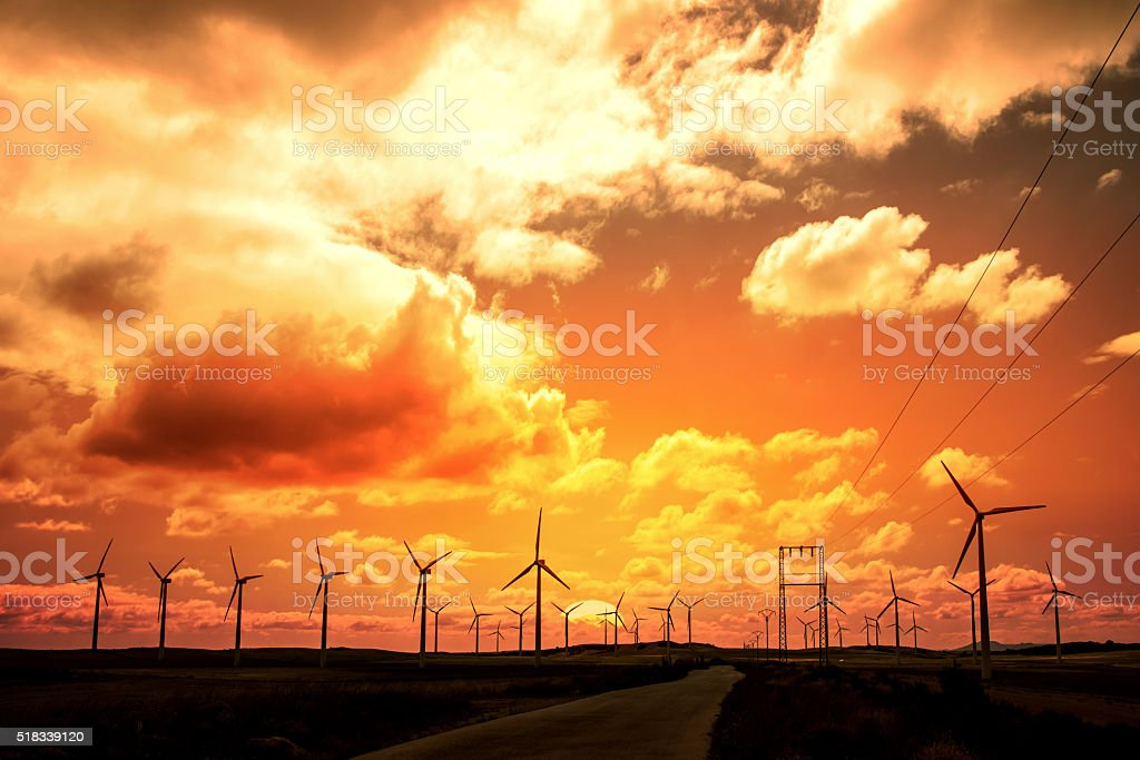 Wind turbine field at sunset, dramatic sky stock photo