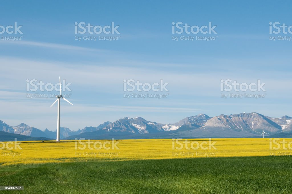 Wind turbine in a field amongst a mountain range stock photo