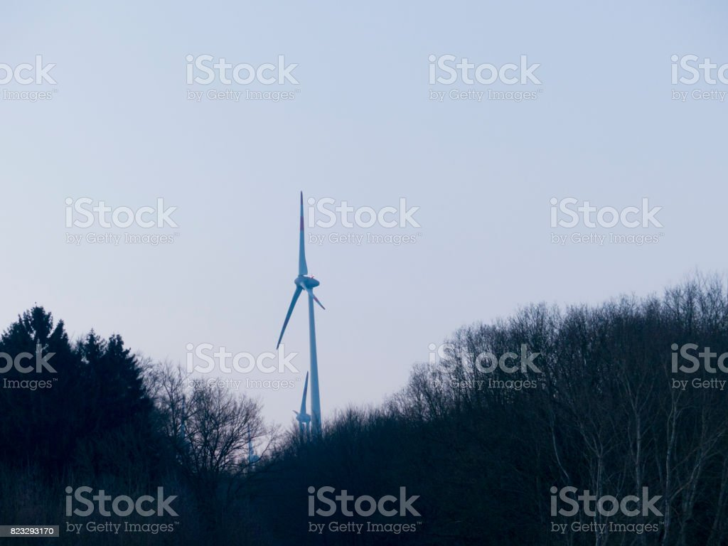 Wind turbine in operation in the forest stock photo