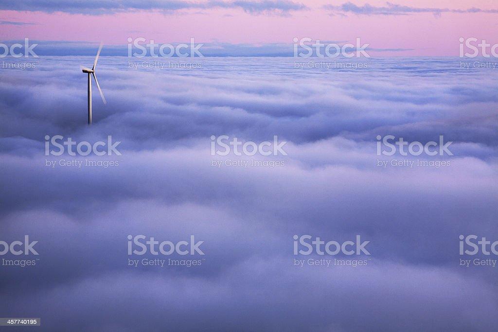 Wind turbine in the clouds stock photo