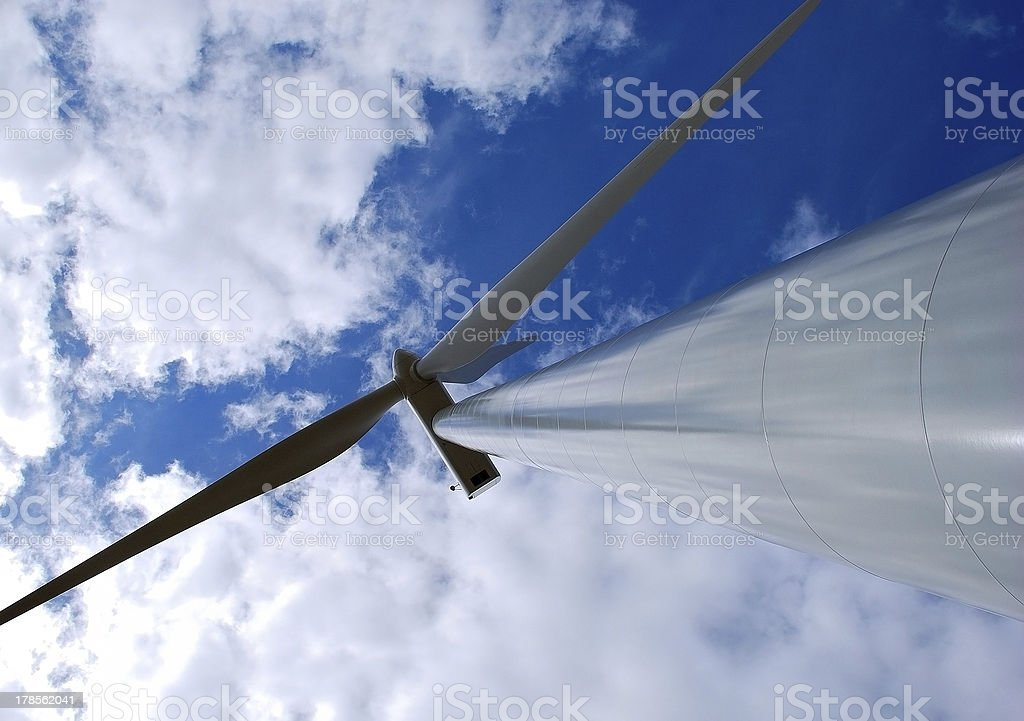 Wind turbine on blue and cloudy sky royalty-free stock photo