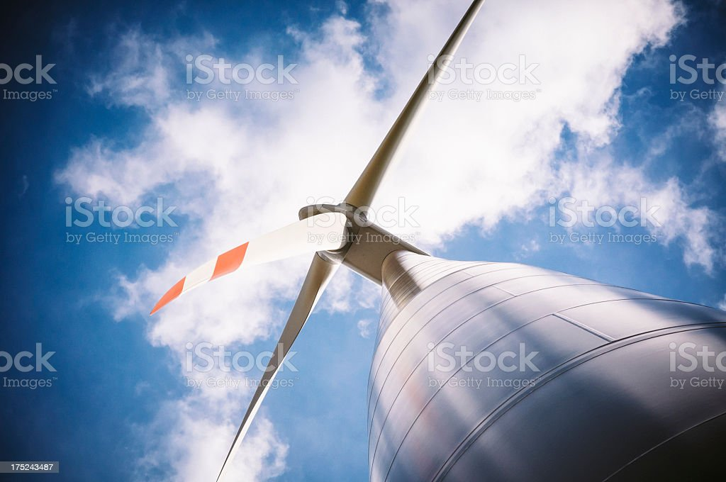 Wind turbine with a dark blue and cloudy sky royalty-free stock photo