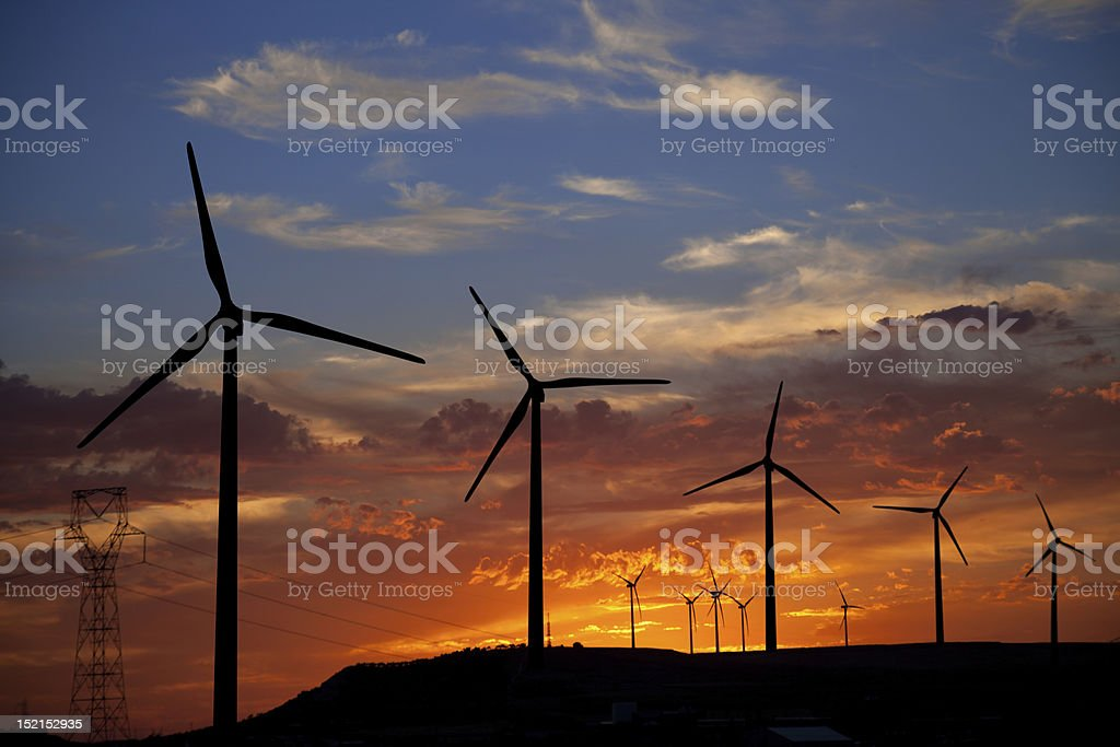 Wind turbines against a fiery sunset stock photo