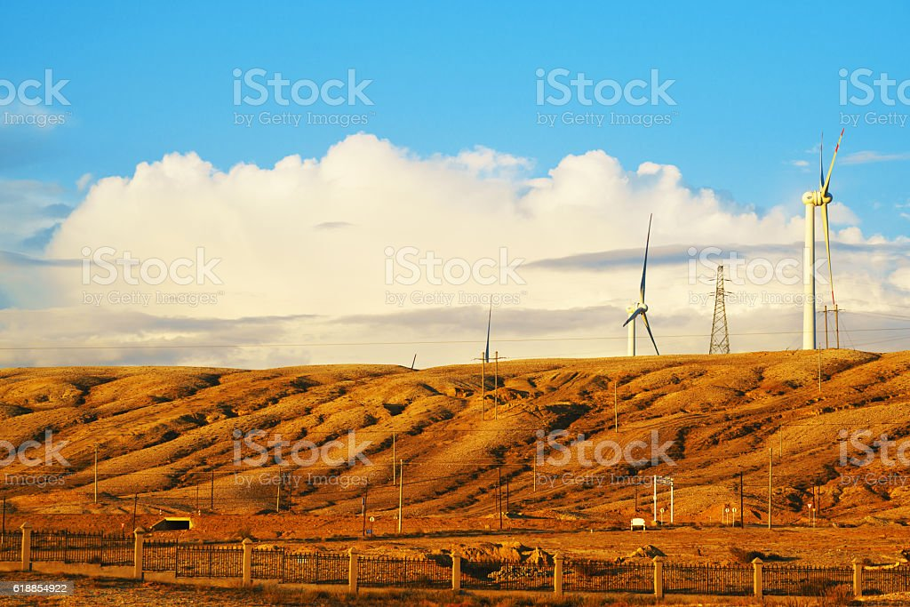 Wind turbines against blue sky in rural field, Xinjiang, China stock photo