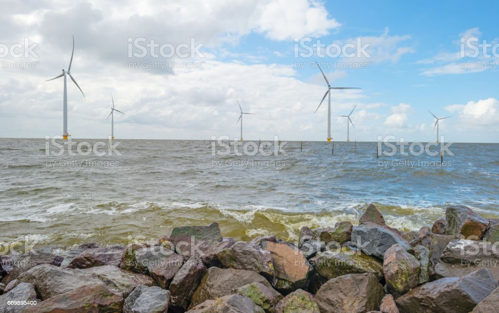 Wind turbines along a dike in spring stock photo