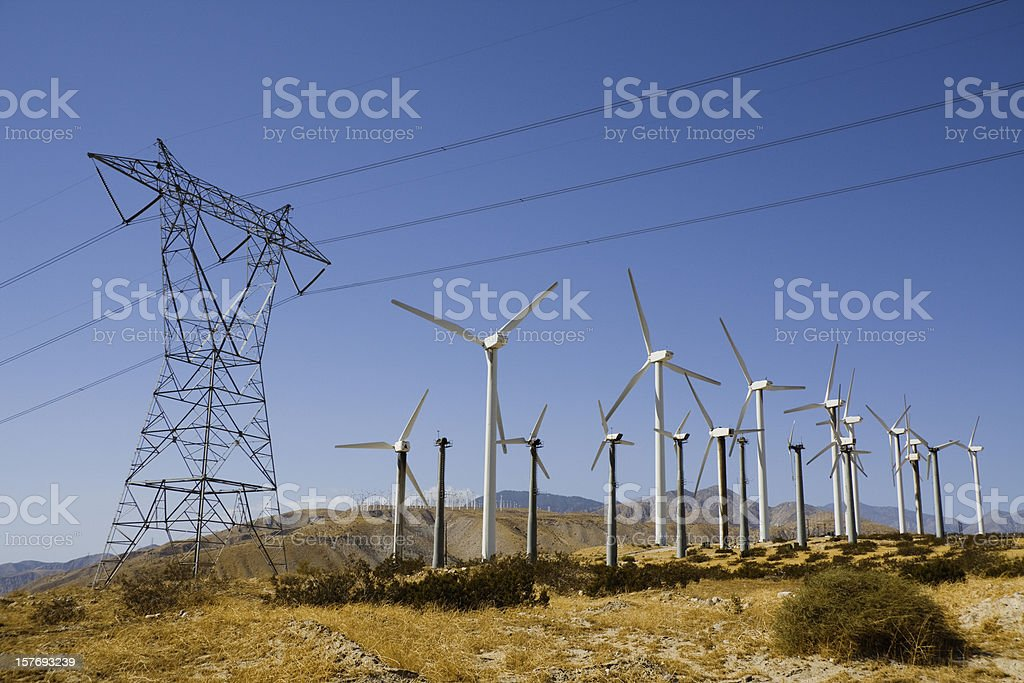 Wind turbines and pylon against a blue sky stock photo