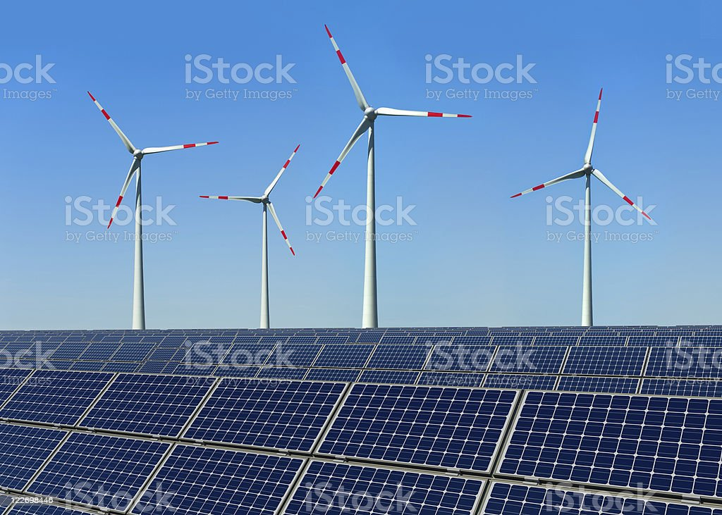 Wind turbines and solar panels against a blue sky stock photo