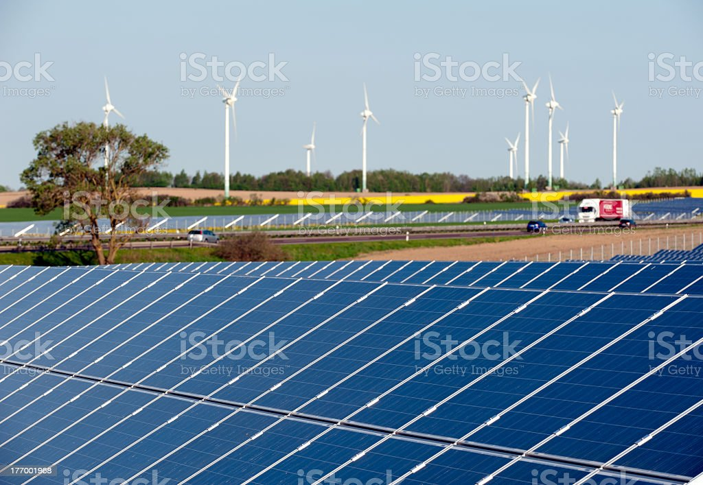 Wind turbines and solar panels in a canola field royalty-free stock photo