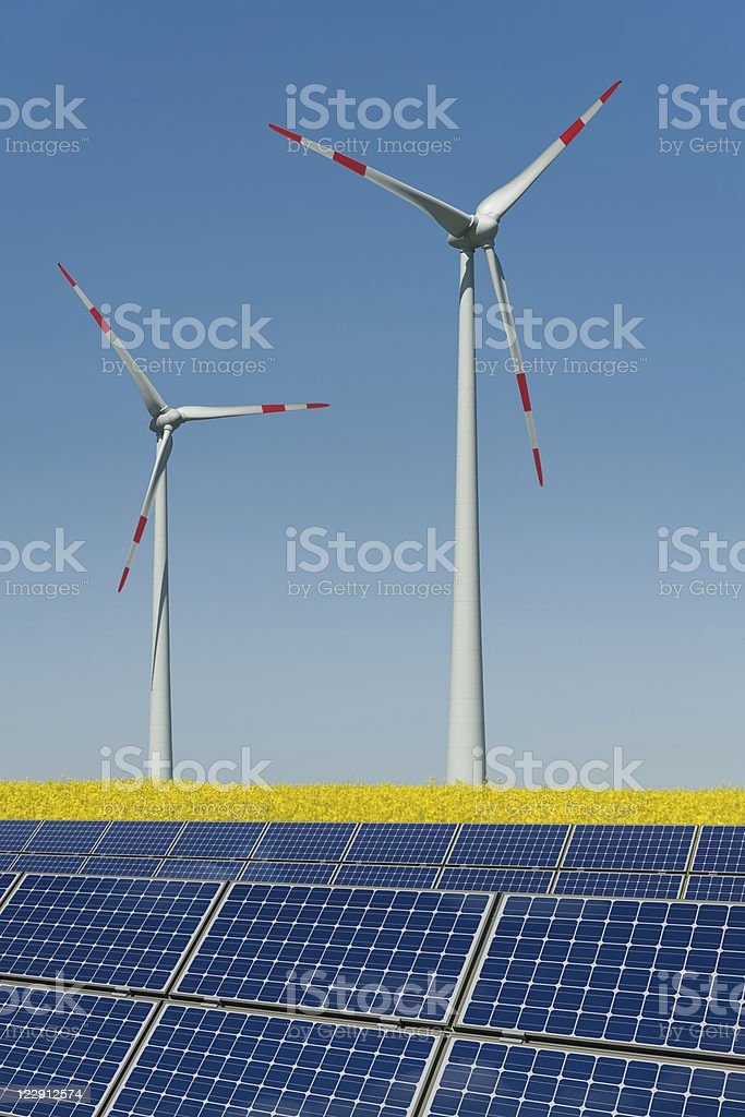 Wind turbines and solar panels in a rapeseed field royalty-free stock photo