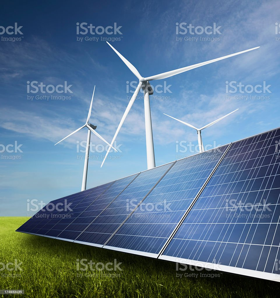 Wind turbines and solar panels on green grass with blue sky royalty-free stock photo