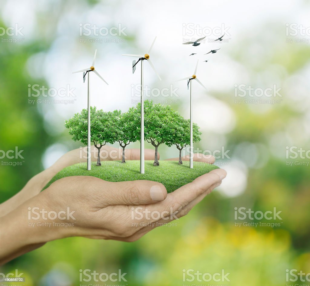 Wind turbines and trees on hands, Ecological concept stock photo
