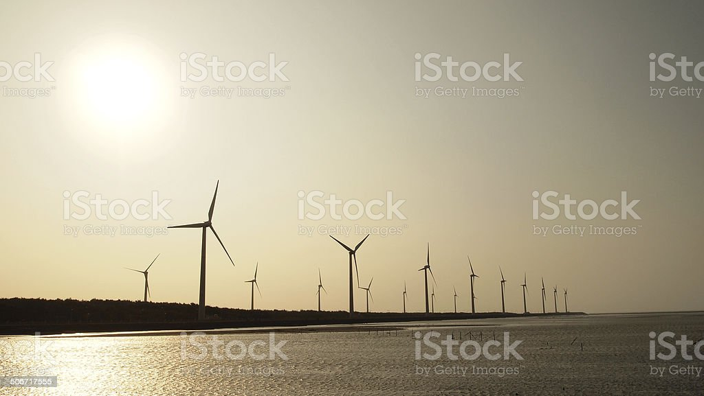 Wind Turbines below the sunset stock photo