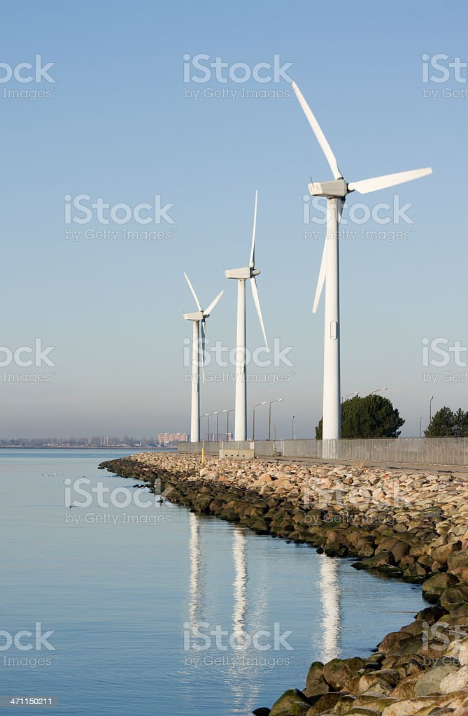 Wind turbines by the water, clear blue sky. royalty-free stock photo