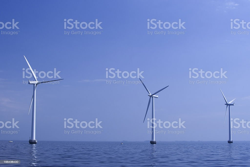 Wind turbines in a row at the ocean outside Copenhagen stock photo