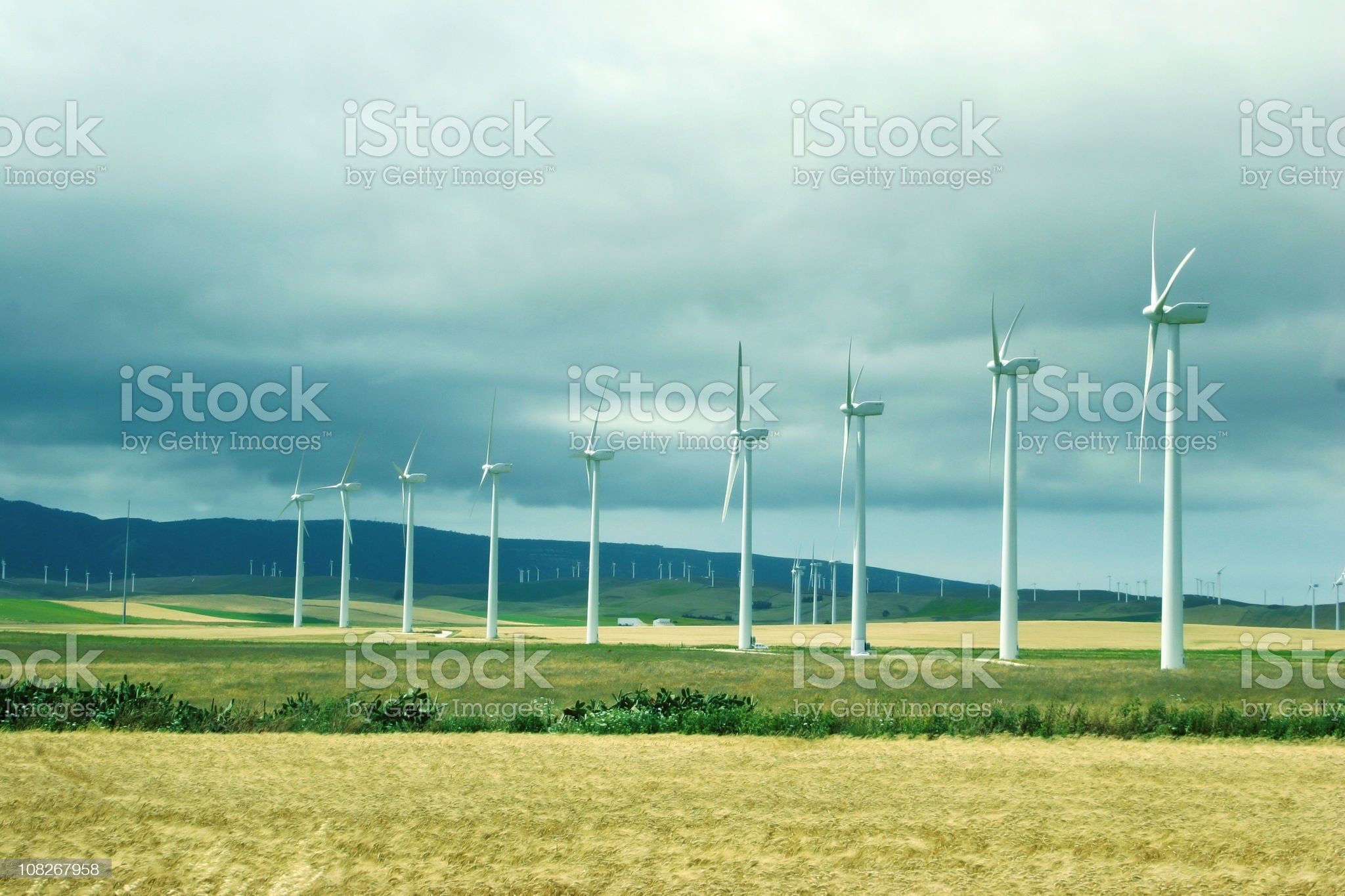 Wind Turbines in Field Near Mountains royalty-free stock photo