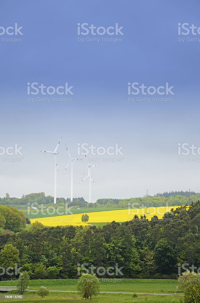 Wind turbines in hilly landscape with canola field royalty-free stock photo