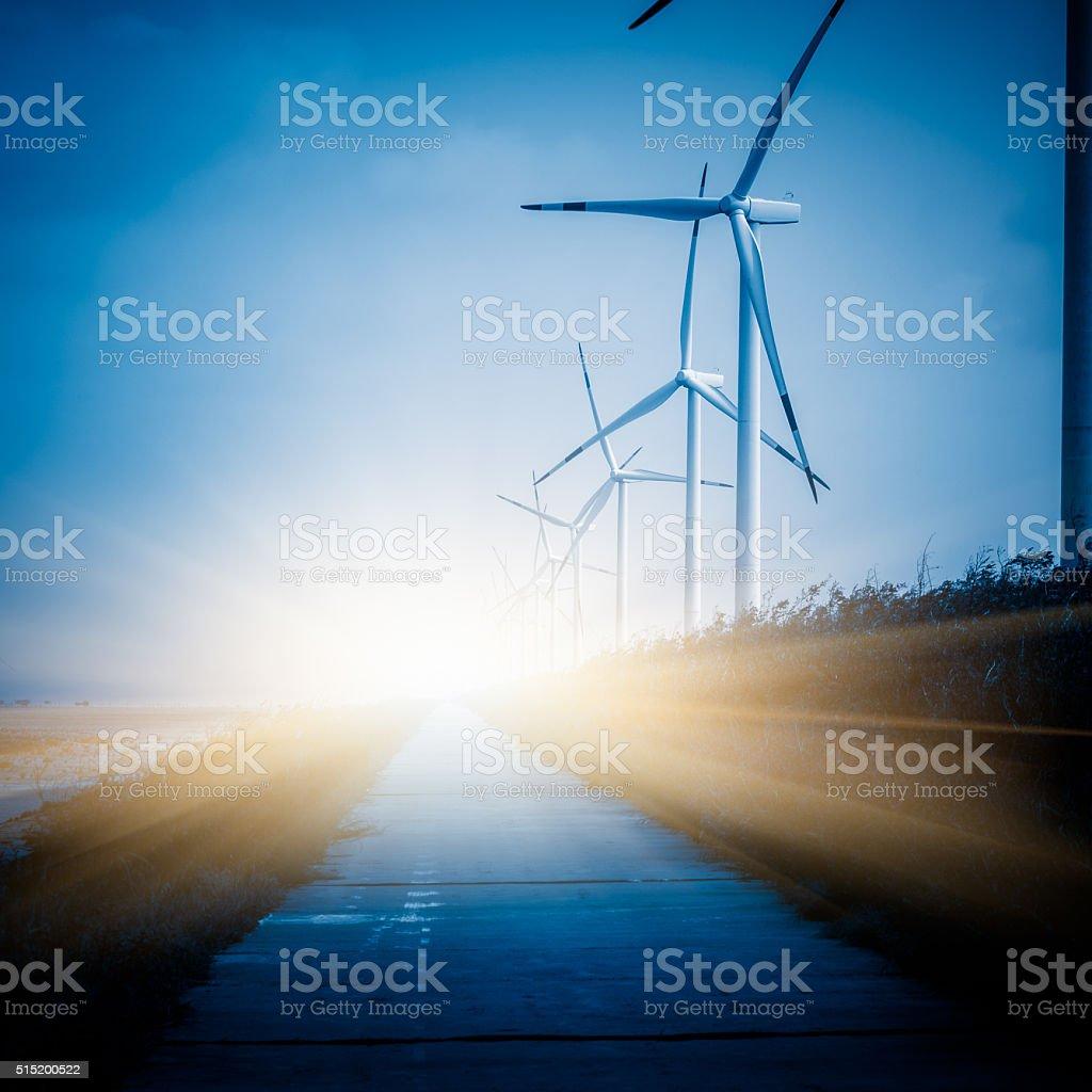 Wind turbines on landscape along empty road against sky stock photo