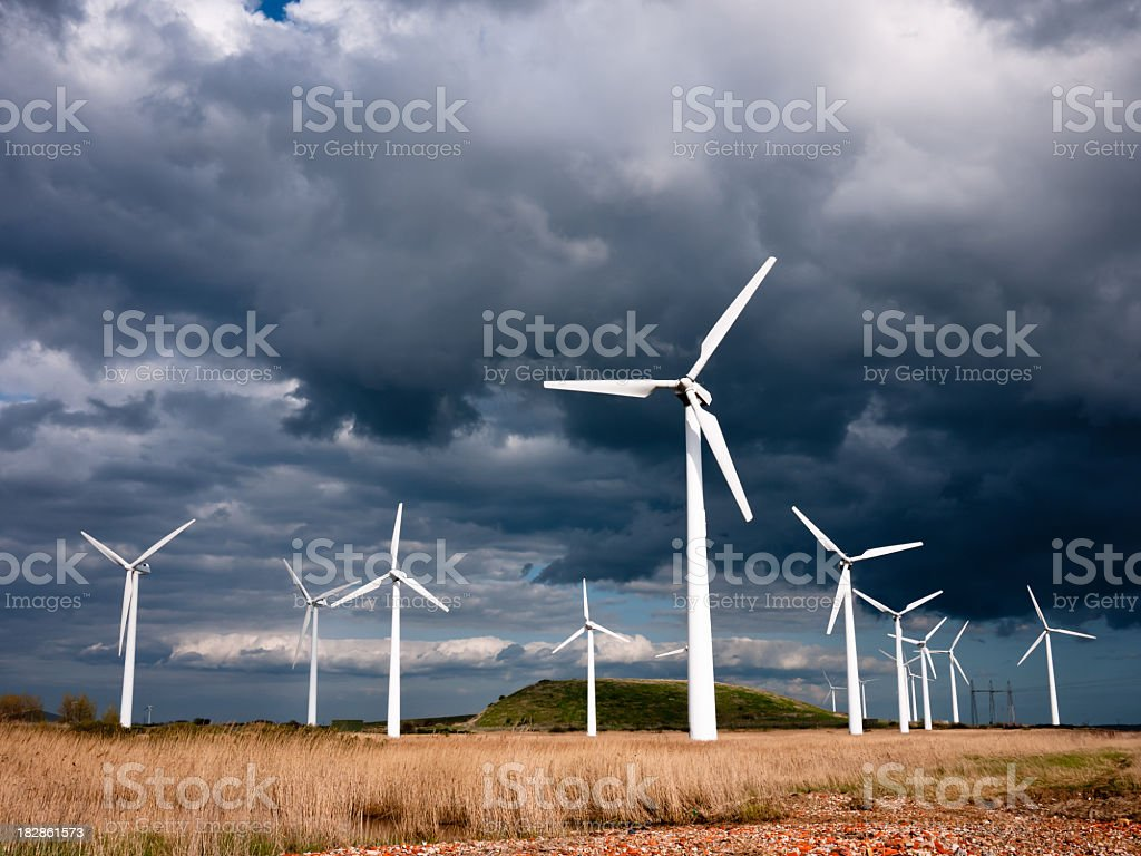 Wind turbines photographed against a dark, stormy sky stock photo