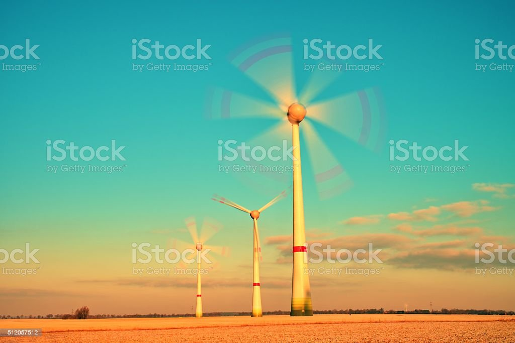 Wind Turbines Producing Electric Energy in sunny spring morning stock photo