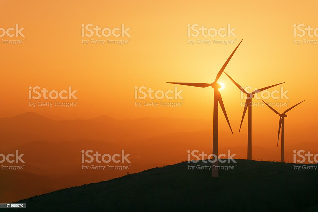 wind turbines silhouette on mountain at sunset stock photo