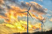 Wind turbines under dramatic sky at sunset