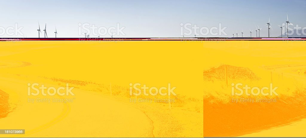 Wind turbines, winding road, and cyclists royalty-free stock photo