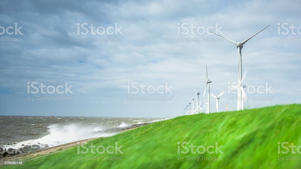 Windfarm with cloudy sky on a dike in the Netherlands stock photo