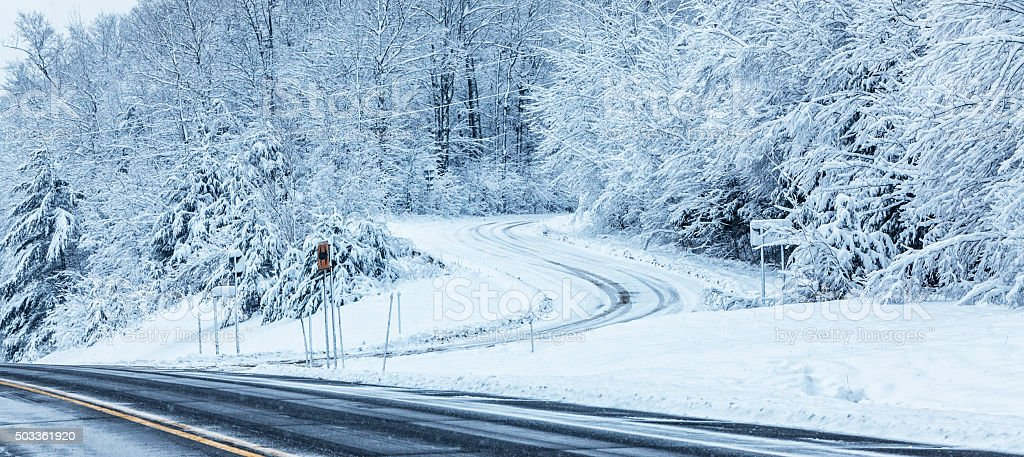 Winding Adirondacks Country Road Intersection During Blizzard Snow Storm stock photo