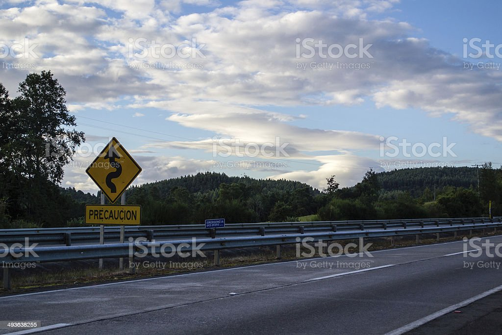 Winding caution sign on highway in wilderness stock photo