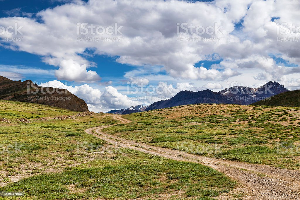 Winding dirt road among green meadows going to snow peaks stock photo