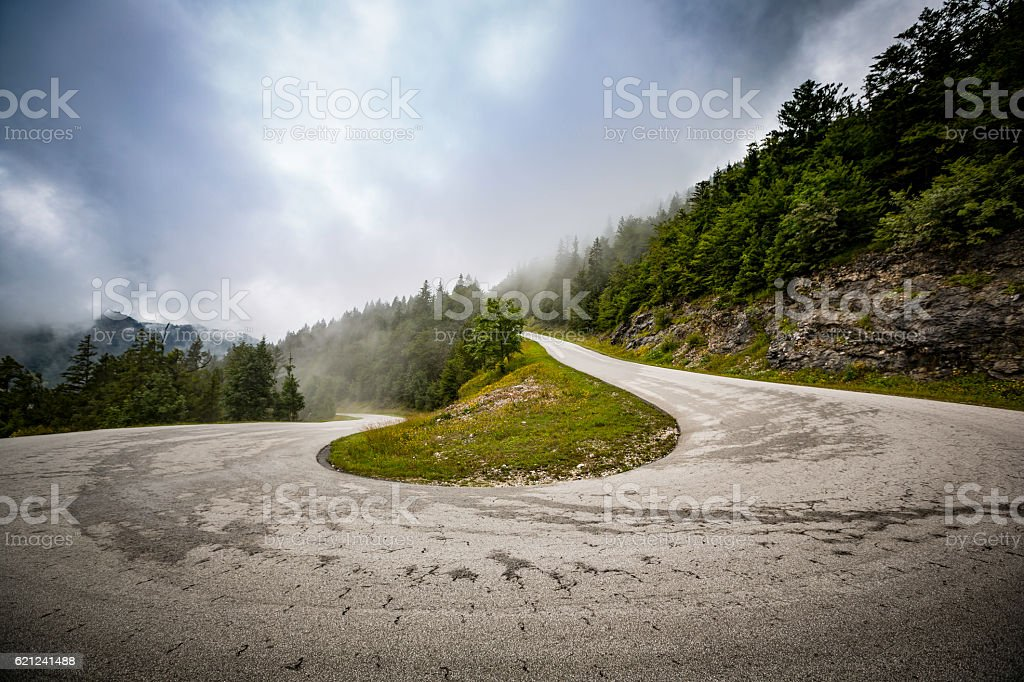 winding mountain road in the clouds stock photo