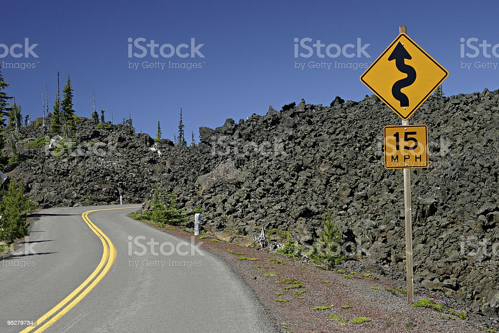 Winding Road And Curves Ahead Sign Through Lava Fields stock photo