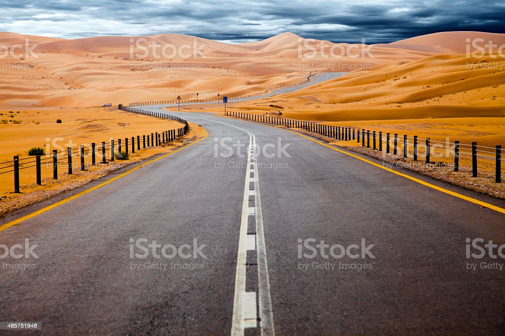 Winding road and sand dunes in Liwa, United Arab Emirates stock photo