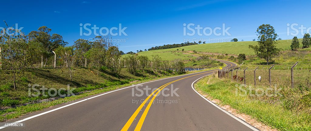 Winding road with no cars and a blue sky stock photo