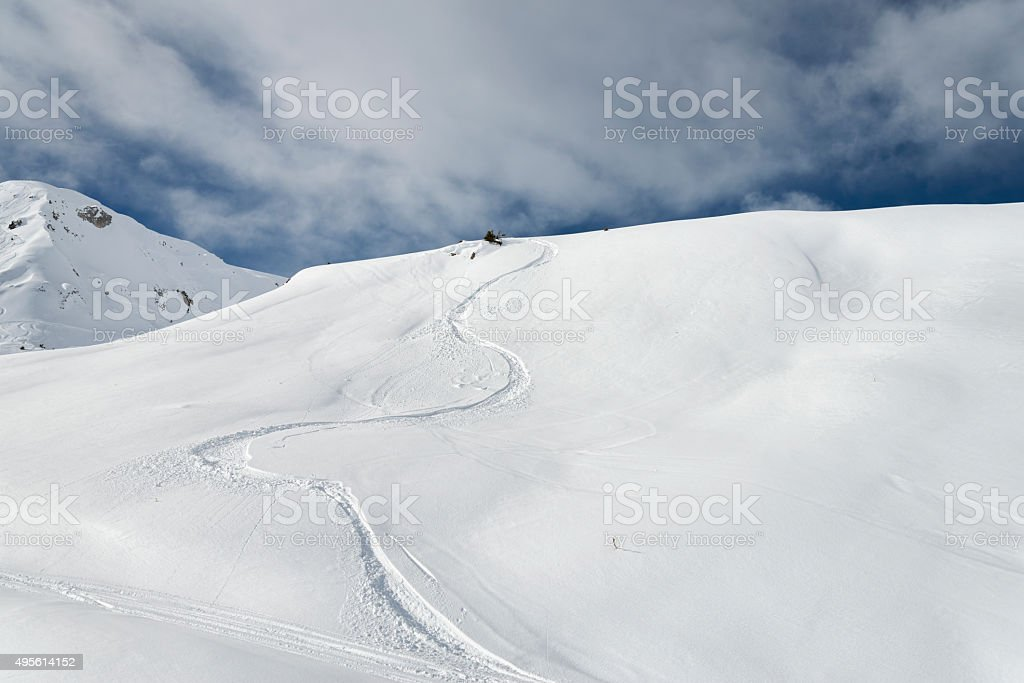 Winding snowboard trail among virgin snow mountains stock photo