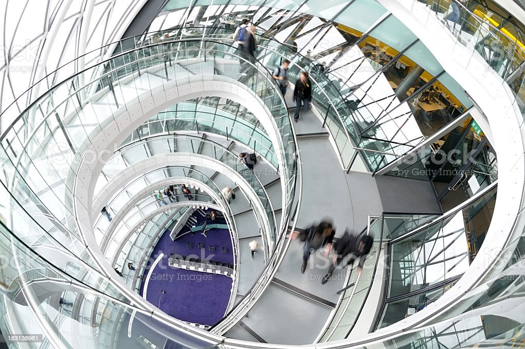 A winding stairwell and people in motion at London City Hall stock photo
