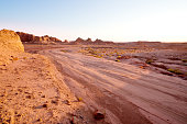Winding unpaved road leading through the yardang field at sunset