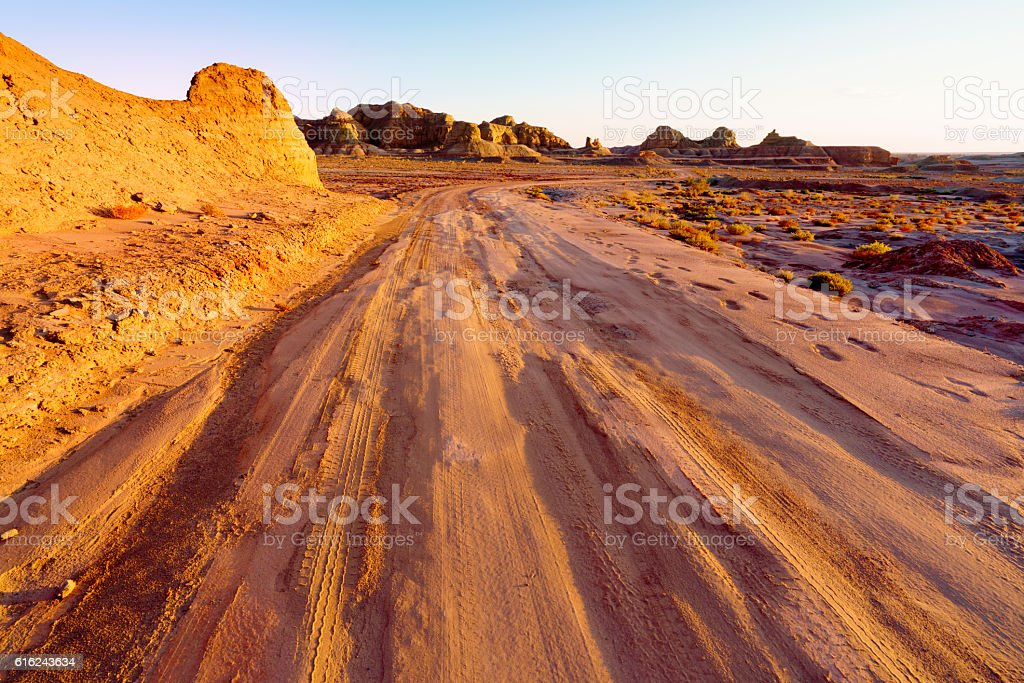 Winding unpaved road leading through the yardang field at sunset stock photo