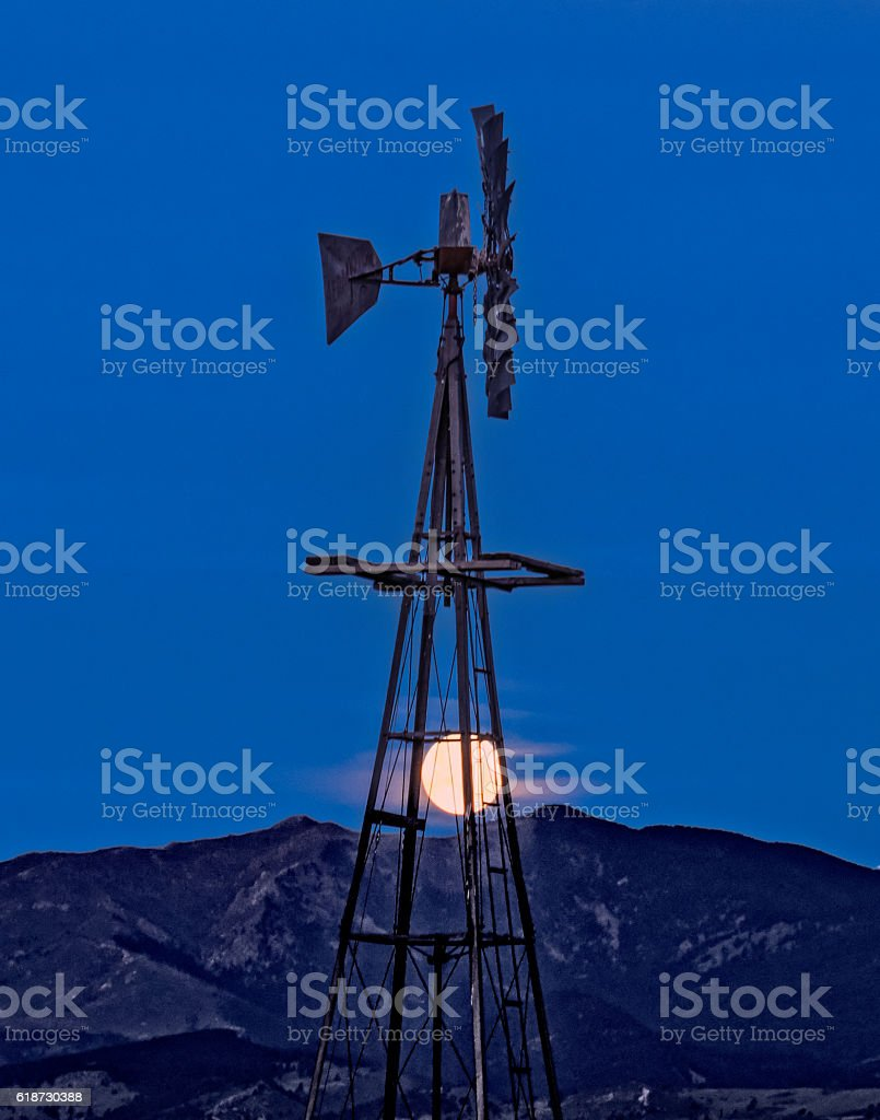 Windmill and moon and mountain range stock photo