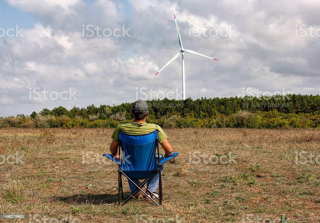 Windmill and young man in chair stock photo