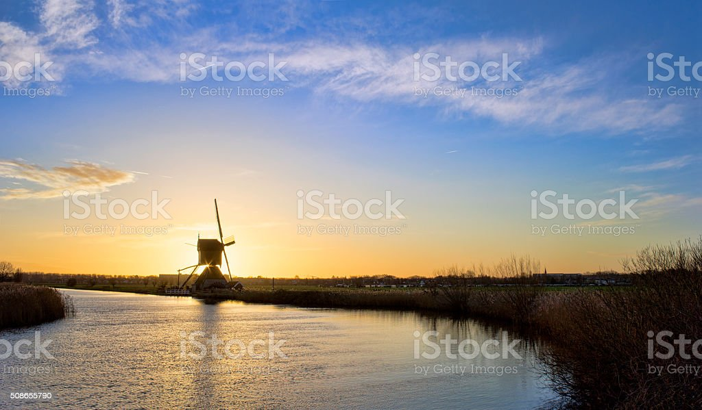 Windmill at sunset at Kinderdijk, The Netherlands stock photo